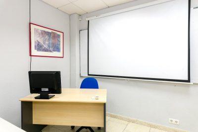 Mesa profesor/a con ordenador y pizarra